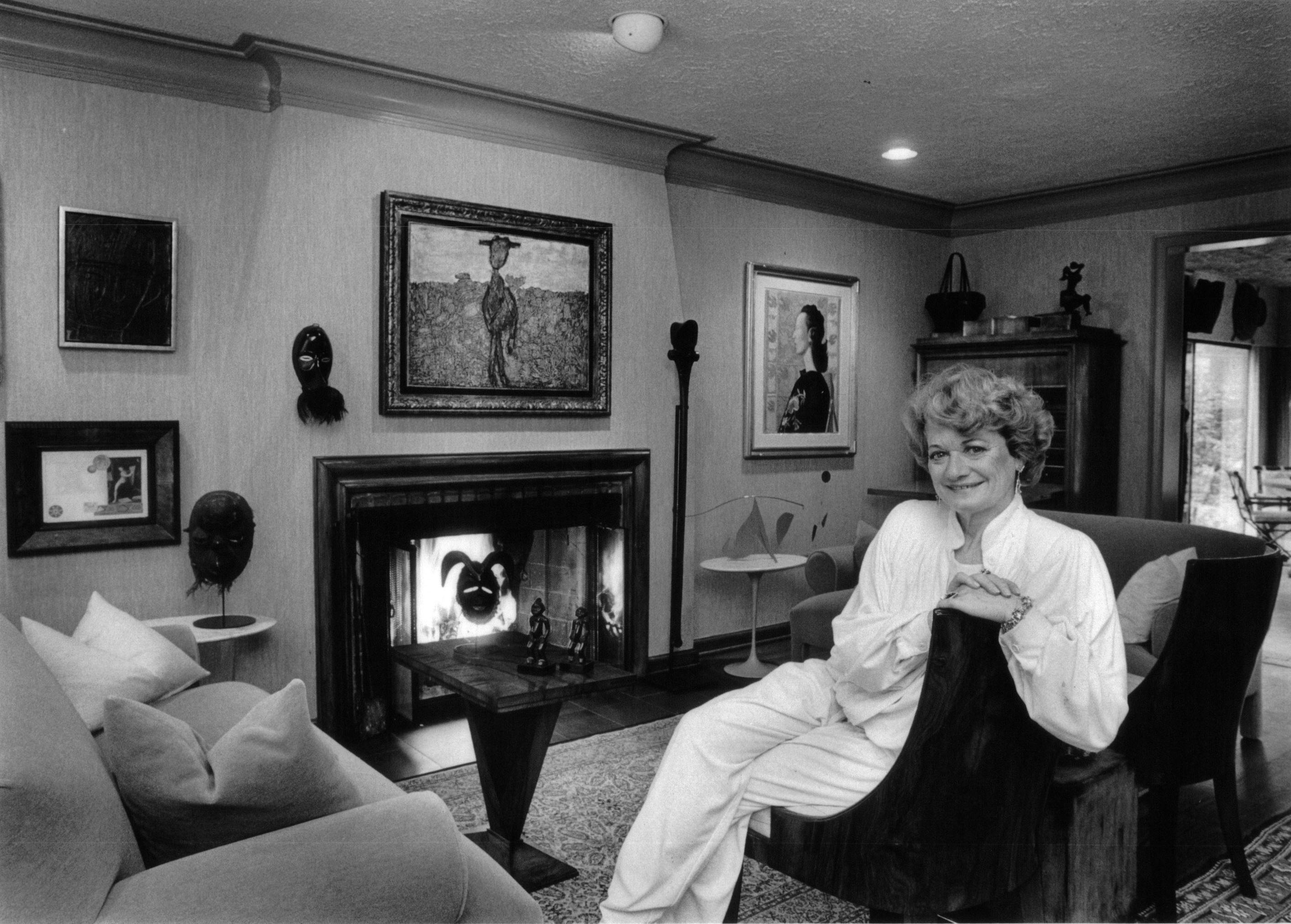 A black and white photo of Margaret Herz Demant in her home, surrounded by her art.