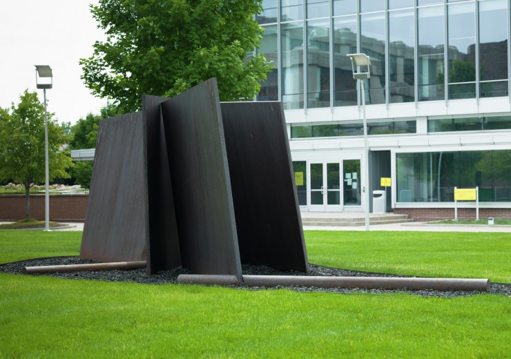 A large steel sculpture with an odd number of thin, flat sides jutting out