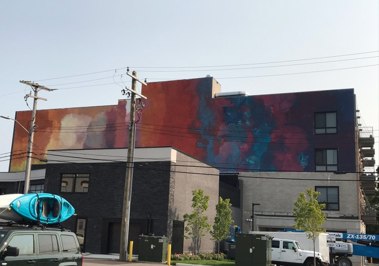 The Lake Orion PIPA mural, an abstract painting of different clouds of colors ranging from red, orange, yellow, purple and blue, as seen from across the street