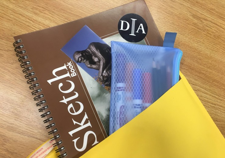 A sketchbook, DIA bookmark, and pouch full of art supplies in a mailing envelope.
