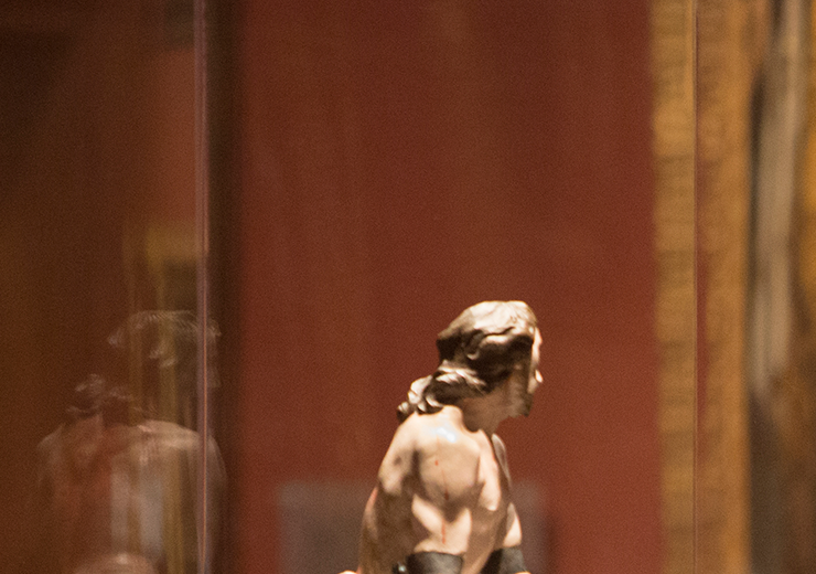 Two young girls observing a small statue behind glass