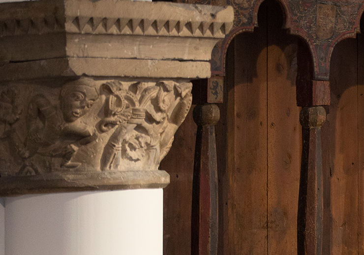 Two patrons talking over a set of old wooden pews in the Romanesque Hall