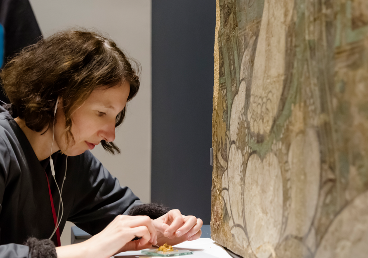 A conservator carefully doing detail work on a large painting in the new Robert and Katherine Jacobs Asian Wing