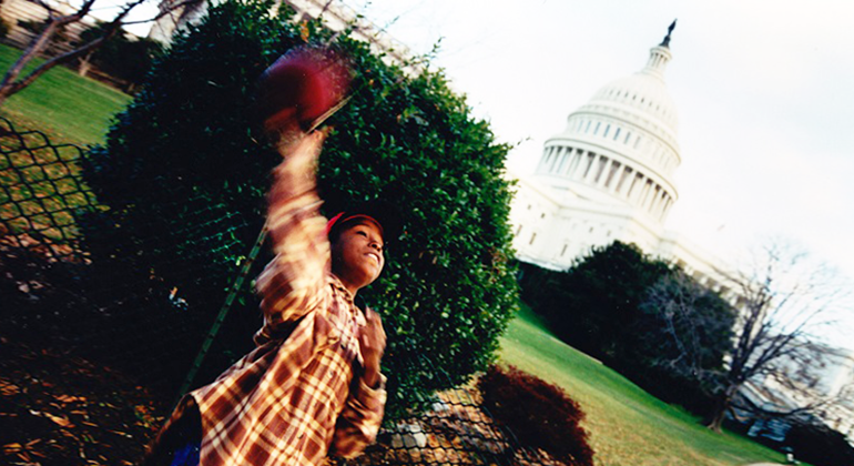 A Black child playing with a ball with the US Capitol building in the background