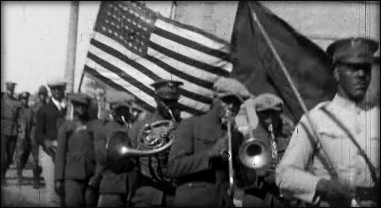 A parade featuring black musicians with the US flag in the background