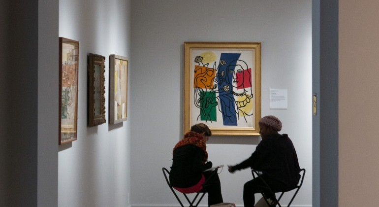 Two patrons drawing in front of an abstract piece