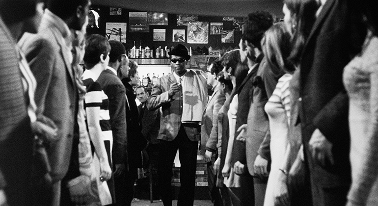 A man stands at the back of an evenly parted crowd in a bar.