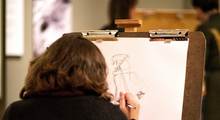 A woman drawing in a gallery
