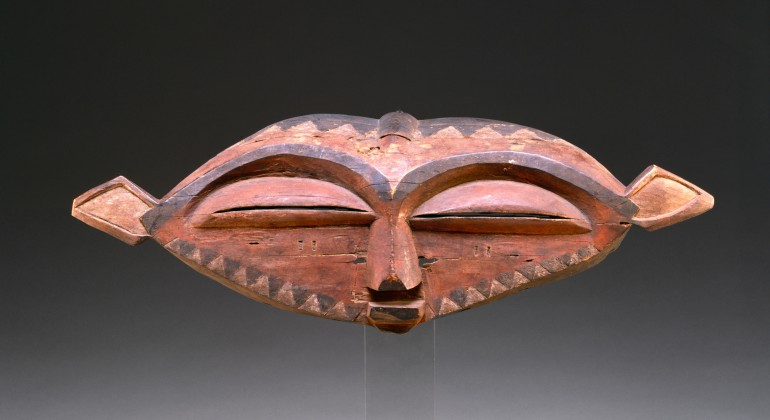 A short, wide wooden mask with black paint around the elongated eyebrows and black and white triangles along the bottom.