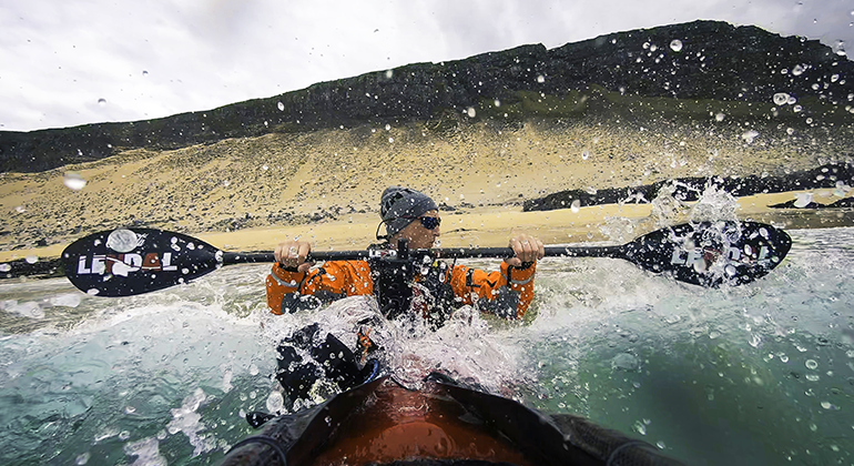 A person using a kayak in rough waters