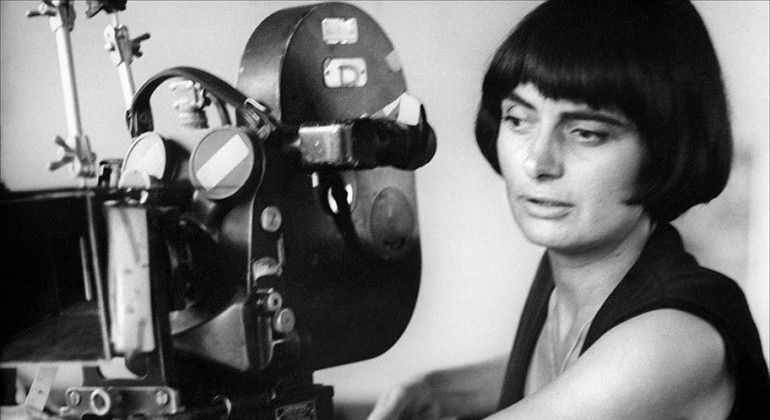 Filmmaker Agnes Varda operating a camera in a black and white photo