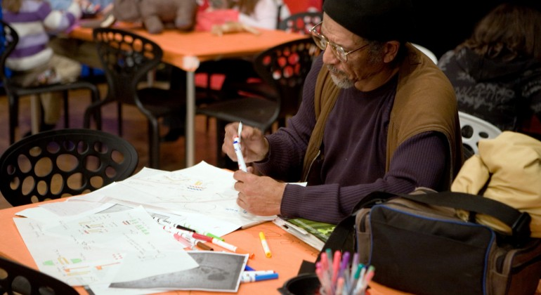 An adult enjoys making an art project in a Drop-In Workshop at the Detroit Institute of Arts