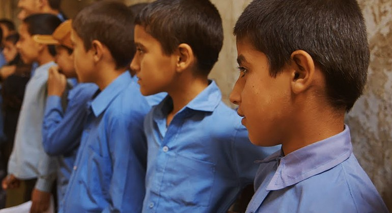 Students in blue polo shirts standing in a line