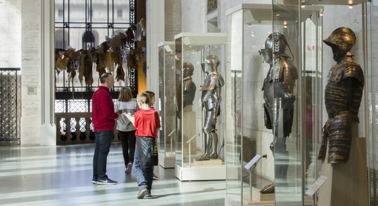 A family with small children looking at the armor cases in the Detroit Institute of Arts' Great Hall