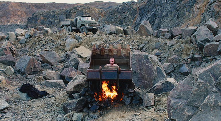 A man sitting in the bowl of a digger, removed from it's truck, which is full of water. A fire roars underneath the digger amidst a rocky landscape.