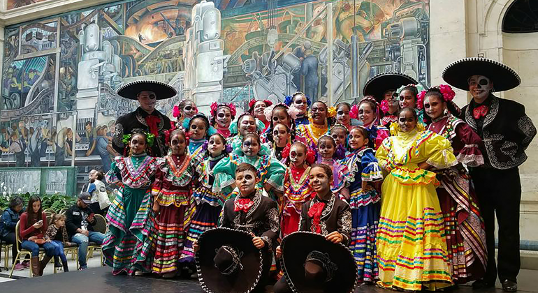 The members of Ballet Folklorico de Detroit in traditional dress, posing for a photograph together in the DIA's Rivera Court.