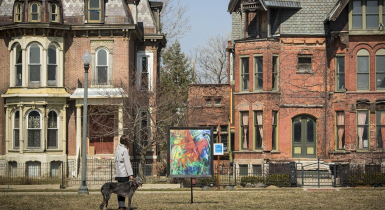 A man and his dog viewing an Inside|Out piece in Brush Park