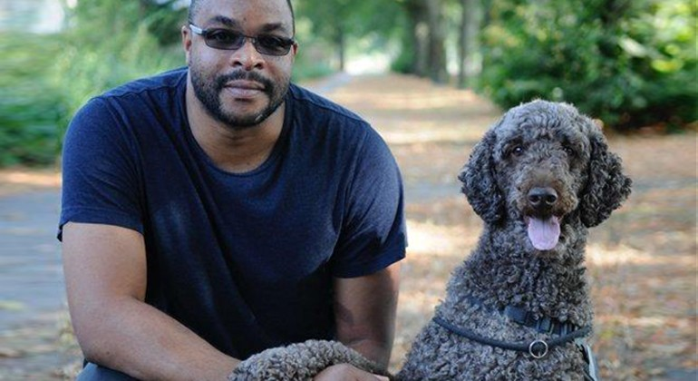 A man sitting next to a gray poodle