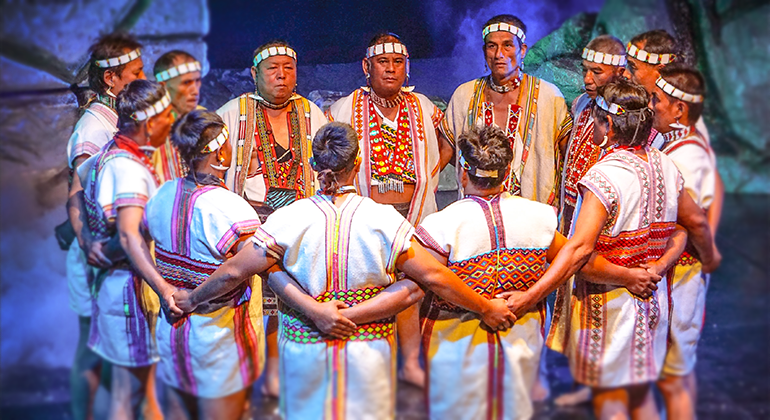 A group of a dozen indigenous Bunun men in traditional white shirts with colorful red beading stand in a circle with their arms around each other's backs.