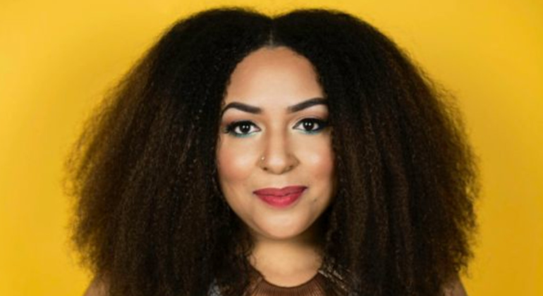 A Black woman, with curly hair, stares straight at the camera in front of a yellow background,