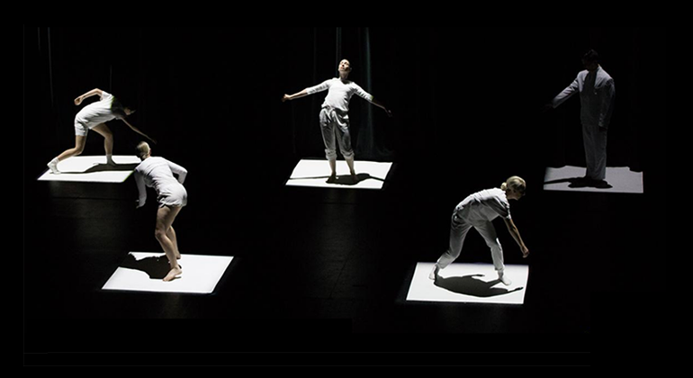Five dancers in white dance on individual white squares (two in front, three in back) spotlighted separately among a dark, black stage.