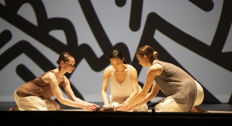 Three people sitting on a stage and presenting a Korean tea ceremony