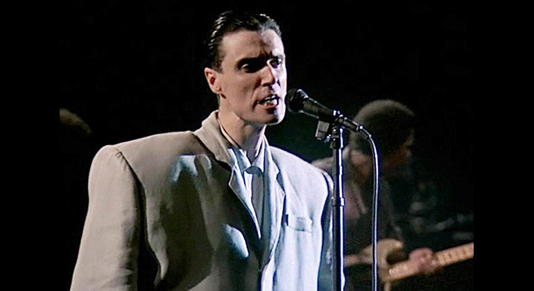 David Byrne in a large suit singing in front of a microphone