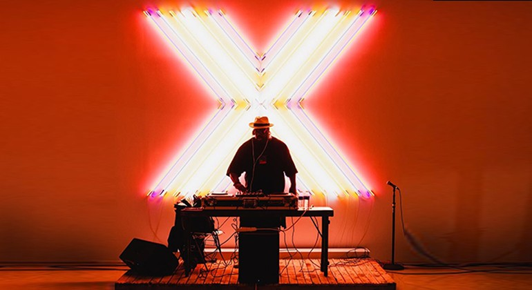 DJ Duane Powell standing behind his equipment in front of a large, glowing X
