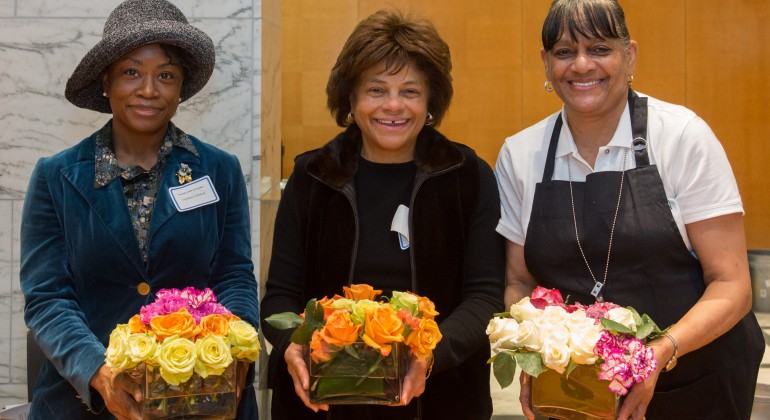 Three members of Friends of Arts and Flowers showing off their flower arrangements