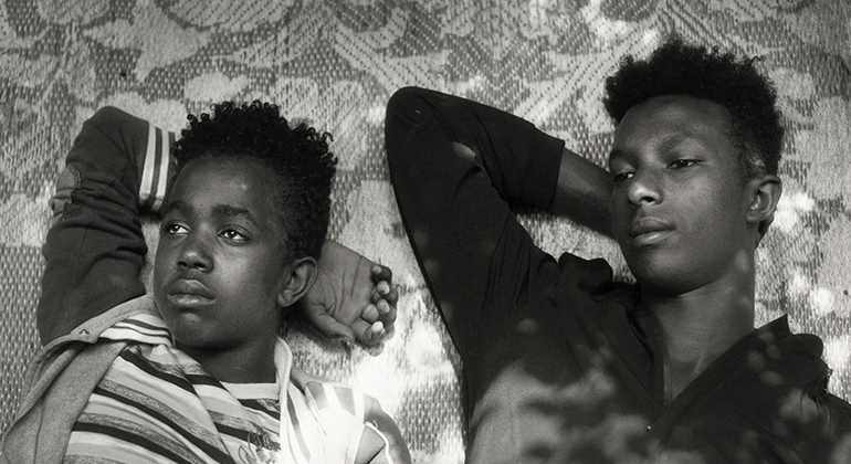Two young Ehtiopian boys laying down side-by-side on a floral rug with their right arms up and tucked under their heads.