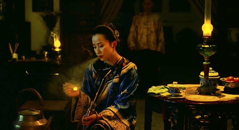 A woman sitting down at a low table lights a match while a figure stands behind her slightly out of focus.