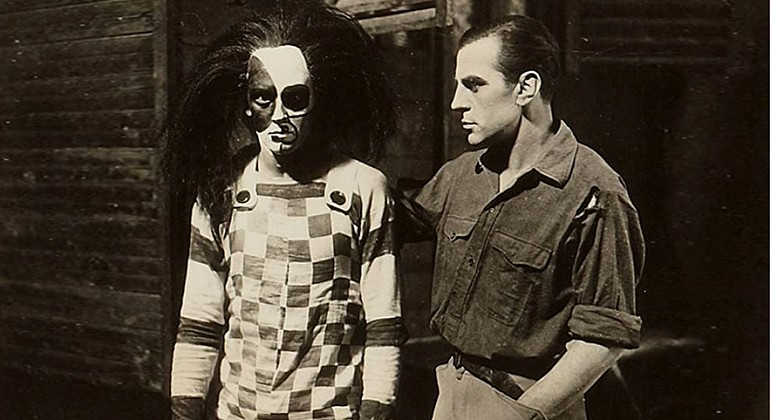 One man in normal dress, and one man in black and white overalls, face makeup and a large black wig