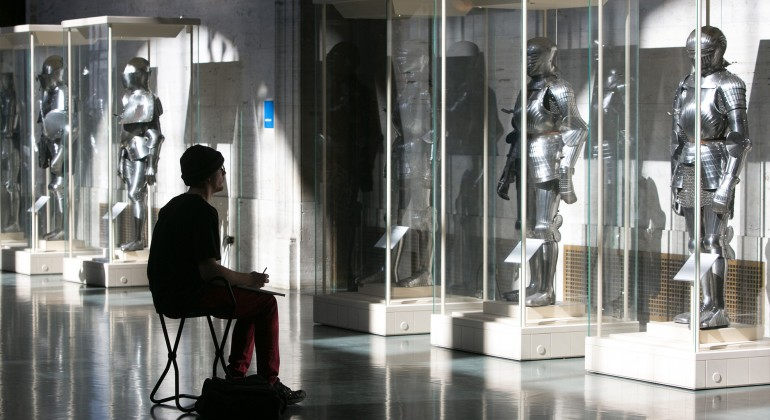 A man drawing in front of the armor cases in the Great Hall