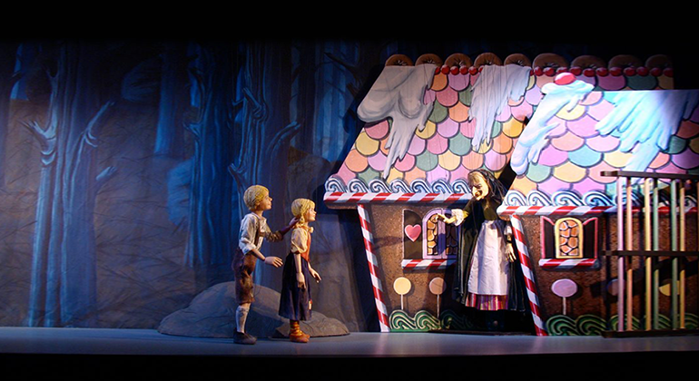 Puppets of Hansel and Gretel as they approach the witches cottage.