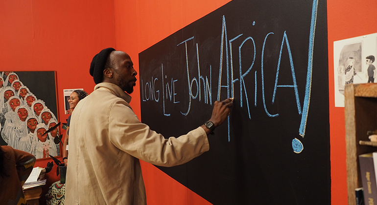 """A Black man in a beanie and khaki jacket writes """"Long Live John Africa!"""" in large, blue and white letter on a chalkboard in a bright orange room."""