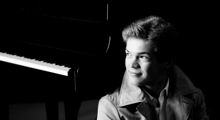 Musician Ivan Moschuk pictured in a trench coat, sitting in front of a piano in this black and white image