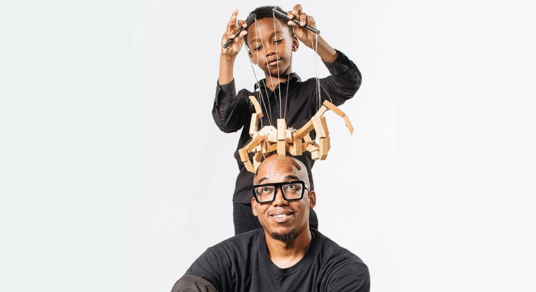 The Jeghetto puppeteer and a young boy playing with a wooden string puppet on the puppeteer's head