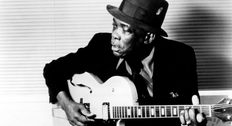 A black and white photo of John Lee Hooker in the 80s playing guitar