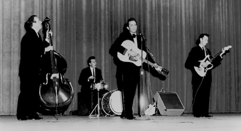An old black and white photo of Johnny Cash performing with a band