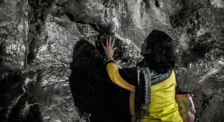 A woman in a yellow jacket with her arms up and hands resting against a large wall of dark rock