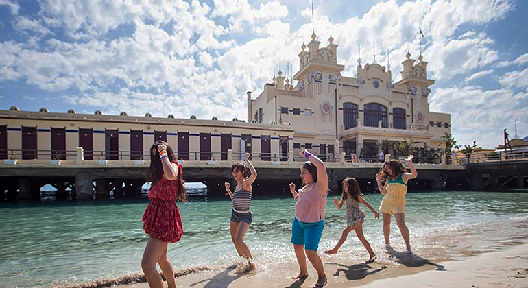 A group of young girls dancing on a water's edge with a building built above the water looming in the background.