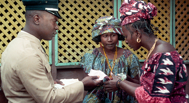 Two women read a note being shown to them by a man in a uniform.