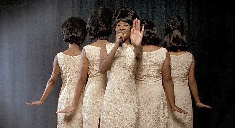 Five women in the same classic Motown outfit, with only one facing front with a microphone