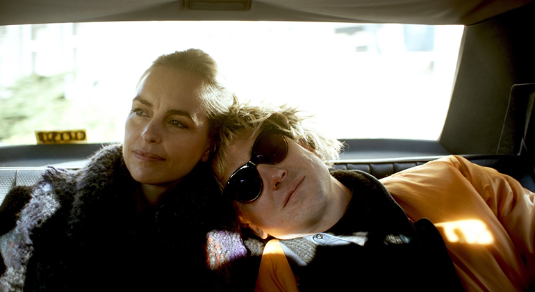Two people sitting in the backseat of a car, leaning against each other while looking away.