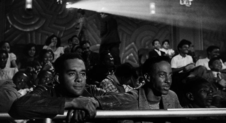 Two masculine presenting black people sitting in the balcony of a theatre, leaning on the railing looking interested with a crowd of moviegoers behind them.