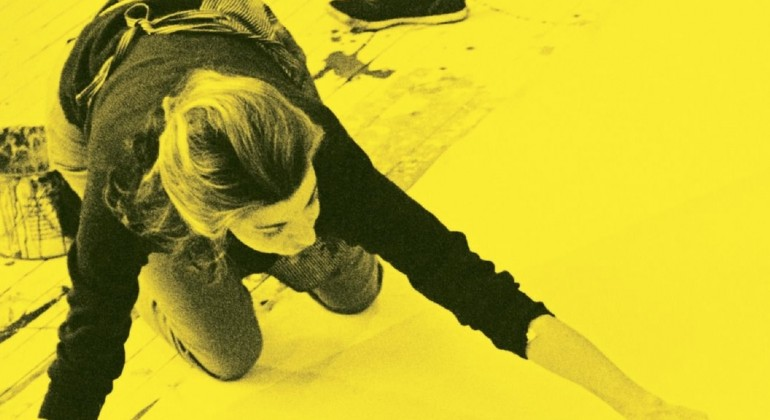 The cover of Ninth Street Women, a woman painting on the floor, with a bright yellow overtone