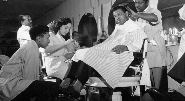 A black and white image of a group of African American people at a barbershop while one man works on the hair of another.