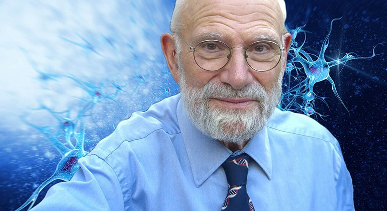In the foreground is Oliver Sacks, a man in a blue button down shirt with a blue tie depicting a double helix of DNA, and a pair of glasses on his face. The background is blue with images of synapses.