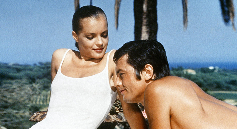 A woman in a white bathing suit and slicked back, wet hair lounges next to a shirtless man with hills and palm trees in the background.