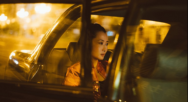 A woman sitting in the back of a car alone